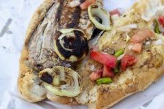 鱼和面包食物特写镜头射击用蕃茄,葱,在街道上的胡椒 免版税图库摄影