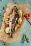 鱼在与菜的纸烘烤了在葡萄酒木桌上 免版税库存图片