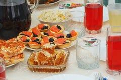 鱼子酱,三文鱼,鳟鱼,蜂蜜,薄饼,在桌上喝 免版税库存图片