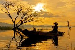鱼小船的剪影渔夫在湖阳光早晨 免版税库存照片