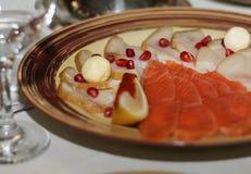 鱼开胃菜板材  装饰用乳酪,石榴种子 库存图片