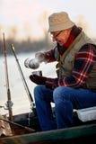 鱼捕鱼冰谎言俄国transbaikalia捕捉冬天 老人坐冷冻湖和饮料茶 库存图片
