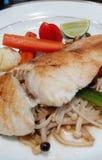 鱼排用金黄蘑菇和柠檬 免版税库存照片