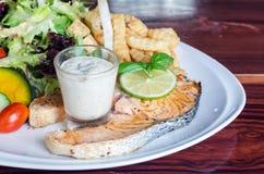 鱼排,烤三文鱼和新鲜蔬菜沙拉,法语星期五 免版税库存照片