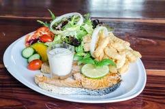 鱼排,烤三文鱼和新鲜蔬菜沙拉,法语星期五 免版税库存图片
