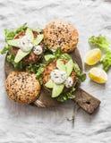 鱼汉堡 与金枪鱼、鲕梨和芥末酱的汉堡用整个在木切板的五谷自创小圆面包在一轻的backgr 免版税库存图片