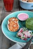 鱼炸肉排用绿色土豆泥 桃红色调味汁和萝卜和microgreens沙拉 西红柿汁 免版税图库摄影