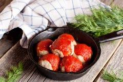鱼糕用tomate调味汁和草本特写镜头在煎锅 免版税库存照片