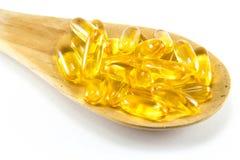 鱼肝油Ω在白色背景隔绝的3个胶凝体胶囊 免版税库存照片