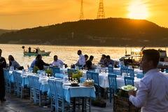 鱼餐馆的游人在阿纳多卢Kavagi村庄海边 库存图片
