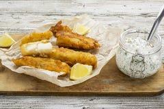 鱼宴-在啤酒面团的鳕鱼用沥青健康和舒适的饮食的沥青调味汁 免版税库存图片