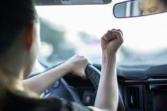 鲁莽的幼小母司机恼怒的路愤怒,在汽车的轮子后 免版税库存图片