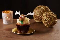 鲁道夫在圣诞节背景的驯鹿杯形蛋糕 库存图片