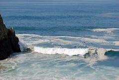 鲍鱼的大海浪和冲浪者在El Morro海滩和水晶Corona del Mar附近指向,加利福尼亚小海湾南部。 库存照片
