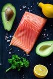鲑鱼排、鲕梨、柠檬、荷兰芹和香料在木切板 库存照片