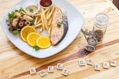 鲑鱼排和炸薯条在一个白色盘投入了 免版税库存照片