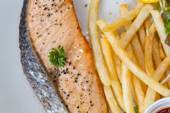 鲑鱼排和炸薯条在一个白色盘投入了 库存图片