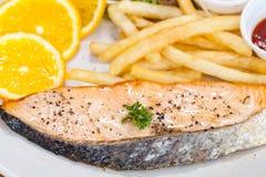 鲑鱼排和炸薯条在一个白色盘投入了 图库摄影
