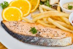 鲑鱼排和炸薯条在一个白色盘投入了 库存照片