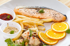 鲑鱼排和炸薯条在一个白色盘投入了 免版税库存图片