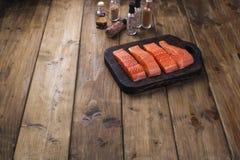 鲑鱼排和香料在小瓶 鲜美和健康食物的准备 木背景和地方文本的 海鲜 免版税库存照片