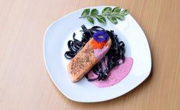 鲑鱼排用油煎鱼獐鹿tobiko的乌贼墨水面团甜菜根奶油沙司 库存图片