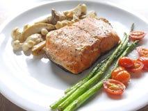 鲑鱼排用芦笋、蕃茄和蘑菇 免版税库存照片