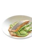 鲑鱼排用豌豆和豆-隔离 库存照片