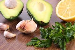 鲕梨、大蒜、柠檬和鲕梨酱或鳄梨调味酱捣碎的鳄梨酱荷兰芹在木背景,成份,健康食物和营养 免版税库存照片