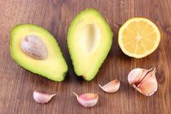 鲕梨、大蒜和鲕梨酱或鳄梨调味酱捣碎的鳄梨酱柠檬在木背景,成份,健康食物和营养 图库摄影