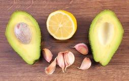 鲕梨、大蒜和鲕梨酱或鳄梨调味酱捣碎的鳄梨酱柠檬在木背景,成份,健康食物和营养 免版税图库摄影