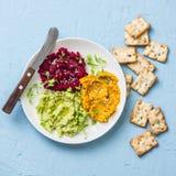 鲕梨、甜菜、姜黄、鸡豆hummus和种子薄脆饼干在蓝色背景,顶视图 可口开胃菜,塔帕纤维布 库存照片