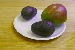 鲕梨和一个芒果在一块白色板材 库存图片