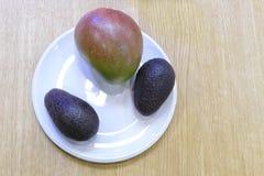 鲕梨和一个芒果在一块白色板材 免版税库存图片