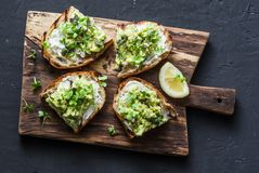 鲕梨和乳清干酪敬酒与在一个切板的微绿色,在黑暗的背景,顶视图 好油脂健康吃概念 图库摄影