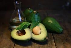 鲕梨和油在木背景 免版税图库摄影