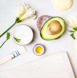 鲕梨和瓶子奶油色油百合花和海盐肥皂白色毛巾在白色背景 鲕梨皮肤护理面膜 库存图片