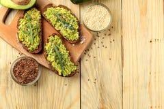 鲕梨和芝麻菜三明治和其他成份在一张自然木桌上 三明治用鲕梨纯汁浓汤 在视图之上 与 免版税库存图片