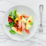 鲕梨和serrano火腿,沙拉开胃菜板材  库存照片