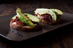 鲕梨多士用五香熏牛肉、乳酪和黑芝麻 库存照片
