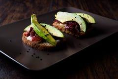 鲕梨多士用五香熏牛肉、乳酪和黑芝麻 库存图片