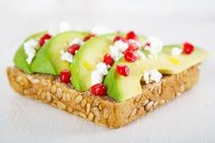 鲕梨用希脂乳,在向日葵种子的石榴在三明治上添面包 库存照片