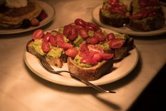 鲕梨鳄梨调味酱捣碎的鳄梨酱多士用在板材的樱桃土豆在厨台 免版税库存照片