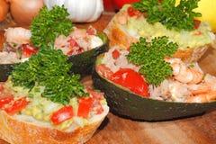 鲕梨, ciabatta,鳄梨调味酱捣碎的鳄梨酱,虾,金枪鱼,蕃茄沙拉 库存照片