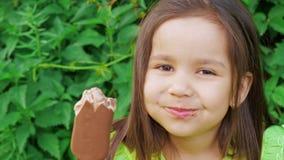 鲜绿色的礼服的一个小逗人喜爱和滑稽的女孩做鬼脸并且吃冰淇淋 影视素材
