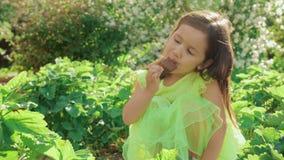 鲜绿色的礼服的一个小逗人喜爱和滑稽的女孩做鬼脸并且吃冰淇淋 股票录像