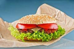 鲜美乳酪汉堡用蕃茄和新鲜的绿色莴苣在蓝色 库存照片