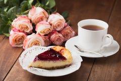 鲜美乳酪蛋糕和一个杯子与玫瑰的热的茶 库存图片
