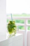鲜美五颜六色的饮料用冷的绿茶、薄菏和柠檬在一个玻璃瓶子在白色厨房背景 免版税库存照片