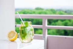 鲜美五颜六色的饮料用冷的绿茶、薄菏和柠檬在一个玻璃瓶子在白色厨房背景 库存图片